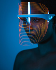 Close-up of woman wearing blue light therapy mask against wall at home