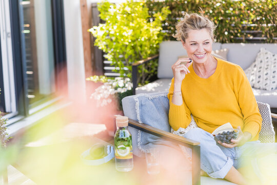 Portrait of happy mature woman sitting on terrace eating blueberries