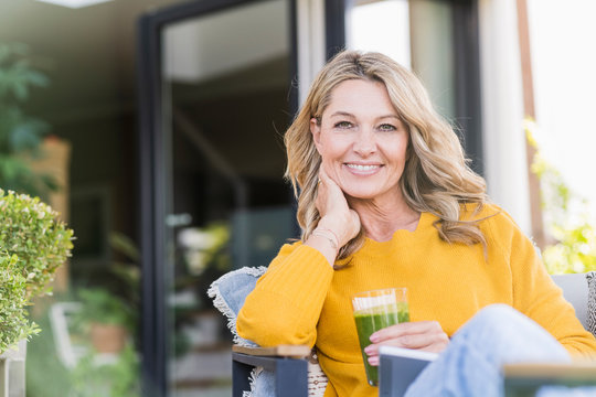 Portrait of happy mature woman sitting on terrace with digital tablet and green smoothie