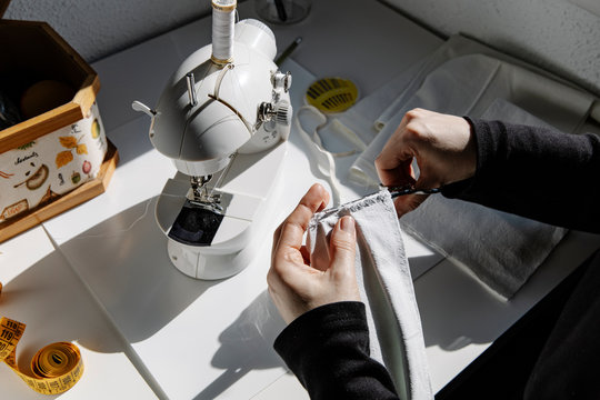 High angle closeup of unrecognizable female sewing nylon elastic band to fabric using needle and threads while creating protective face mask at home