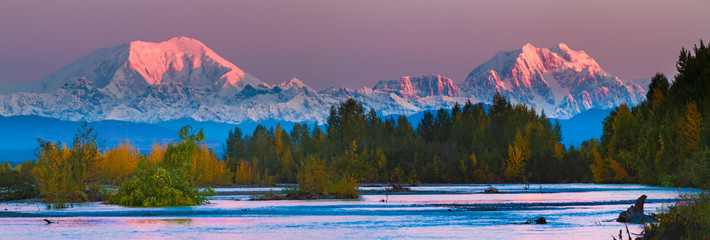 Sunrise on Mt Foraker and Mt Hunter accross the Susitna river with fall foliage. Mount Foraker is a 17,400-foot mountain in the central Alaska Range, in Denali National Park