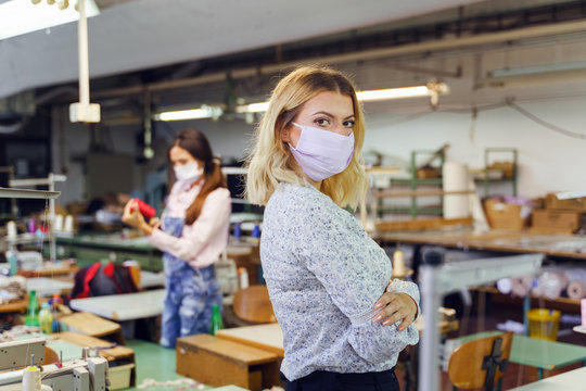 Young adult caucasian woman entrepreneur stand at sewing factory - Female worker designer wearing protective mask at work during pandemic - New normal crisis recession concept covid-19 business