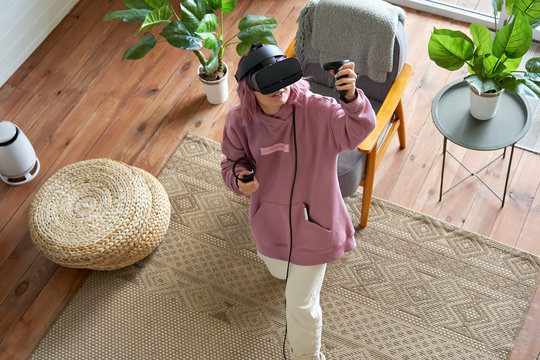 Teen girl pink hair wears vr headset goggles holds controllers plays vr video game futuristic immersive simulator explores virtual reality 3d 360 cyber gaming experience at home looking up, top view.