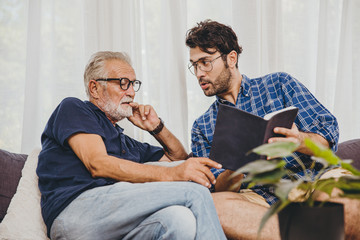 Young man consulting business project or education lecture content in text book with retired senior elder at home