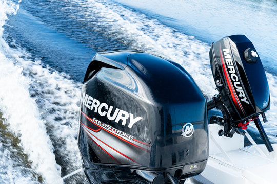 Sankt-Petersburg, Russia, August 8, 2020:  Modern new fishing sport boat with a brand new Mercury FourStroke outboard engine speeding on the lake.