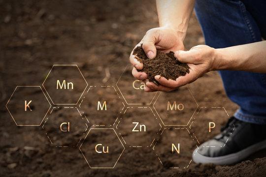 Man testing rich soil outdoors, closeup