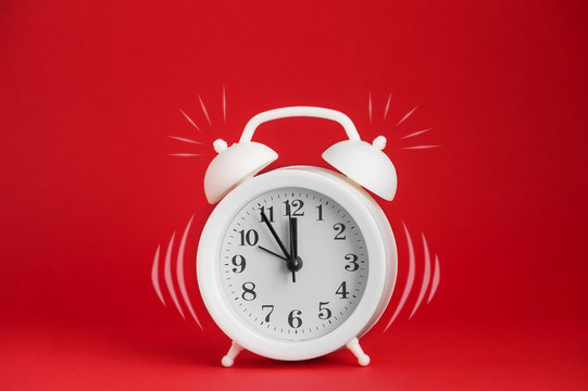 White alarm clock with imitation of the call on the red isolated background. Close-up, copy space. The concept of awakening.