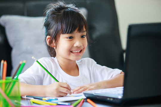 asian girl studying at home with laptop