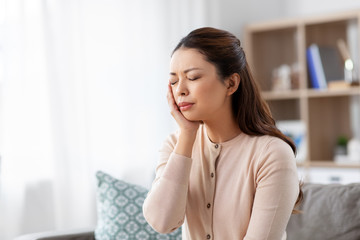 healthcare, dental health and problem concept - unhappy asian woman suffering from toothache at home
