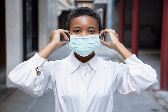 young African woman properly wearing face mask in outdoor public space