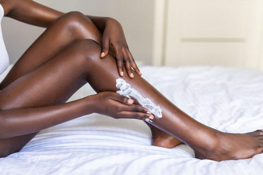 African female putting Moisturizer on her legs
