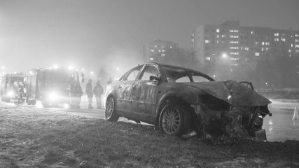 Winter car accident, burned car with fire engine and buildings in the background. High quality photo