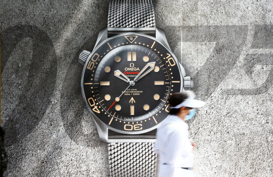 Woman walks past a poster advertising a Seamaster watch of Swiss manufacturer Omega in Zurich