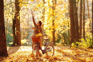 Stylish woman with a bicycle enjoying autumn weather in the park. Beautiful Woman walking  in the...