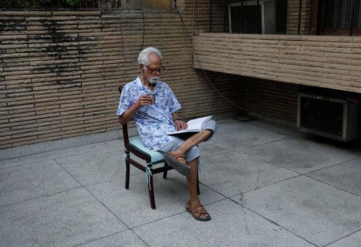 Gopalan Balachandran, maternal uncle of U.S. Senator Kamala Harris' (D-CA) reads a book outside his house in New Delhi