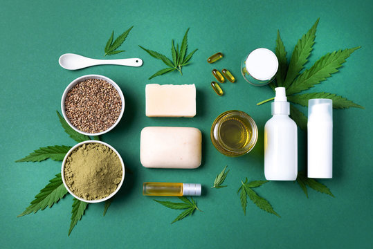Flat lay with hemp extract products - cosmetics, lotion, face cream, body butter, soap bars, cannabis leaves, seeds, hemp oi, capsules, protein powder, flour on green background. Top view. Copy space