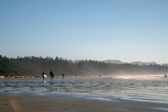 People surfing in Long Beach Tofino in winter