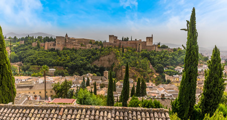 A view from the Saint Nicholas Plaza over the rooftops of the Albaicin district of Granada towards the Alhambra Palace and the Sierra Nevada mountains in the summertime Fotomurales