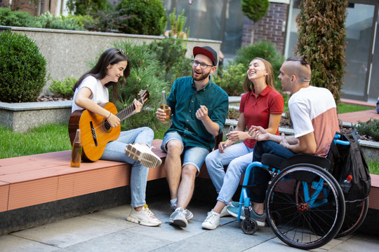 Drinks and songs. Group of friends taking a stroll on city's street in summer day. Handicapped man with friends having fun. Inclusion and diversity concept, normal lifestyle of special groups of