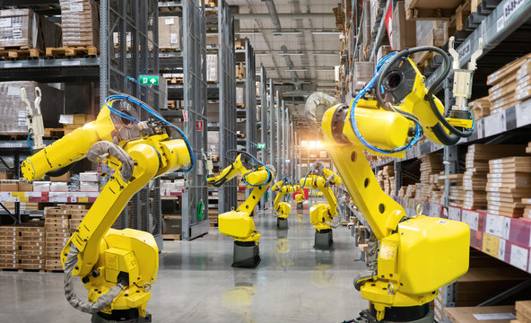 Automatic robot mechanical arm is working in temporary storage in a distribution warehouse.