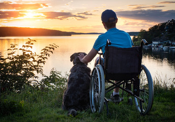 Boy in wheelchair at sunset