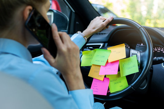 busy day schedule concept - woman driving car with to do list notes on the wheel and talking on the phone