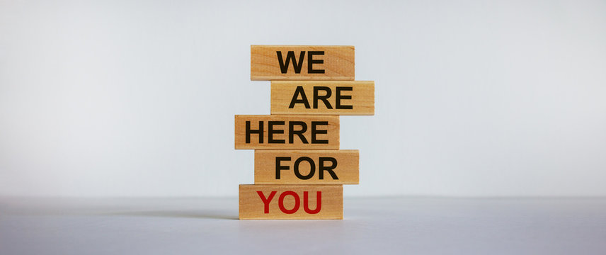 Wooden blocks with text 'we are here for you'. Beautiful white background, copy space. Business concept.