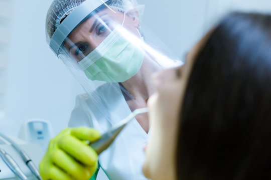 Female dentist wearing  face mask, gloves and visor as coronavirus safety precaution checkup dental health of young woman