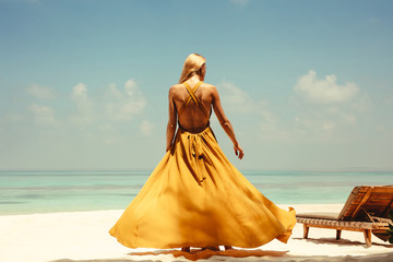 Rear view of young woman in yellow dress standing on beach