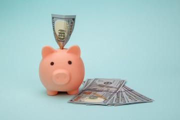 Piggy bank with money banknotes on blue background. Savings concept.