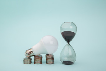 Light bulb with coins stack on blue background. Power energy concept.