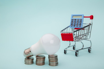 Light bulb with coins stack and trolley with calculator on blue background. Energy saving concept.