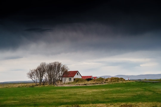 Icelandic Cottage house under the ominous dark clouds