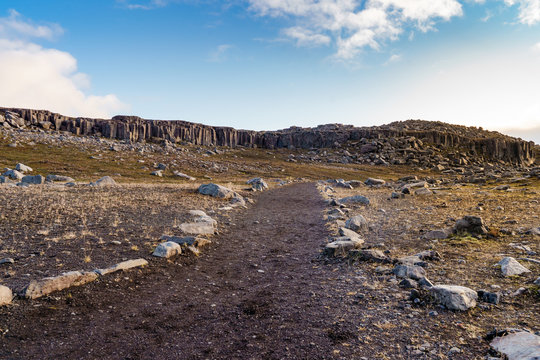 Into the wild. The isolated road leading into the unknown of the basalt columns in Iceland rural area.
