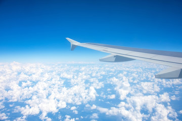 Airplane flying above the summer clouds, aerial wing view. Fotobehang