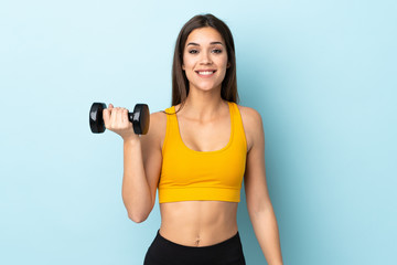 Young caucasian woman making weightlifting isolated on blue background with surprise and shocked facial expression