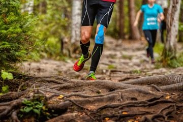 Wall Mural - legs man runner in compression socks and kinesio taping on knee run forest trail