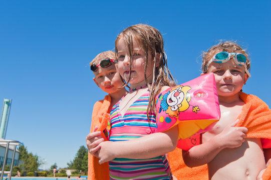 drei Kinder in Badesachen mit orangem Badetuch