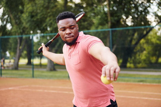 African american man in pink shirt plays tennis on the court outdoors