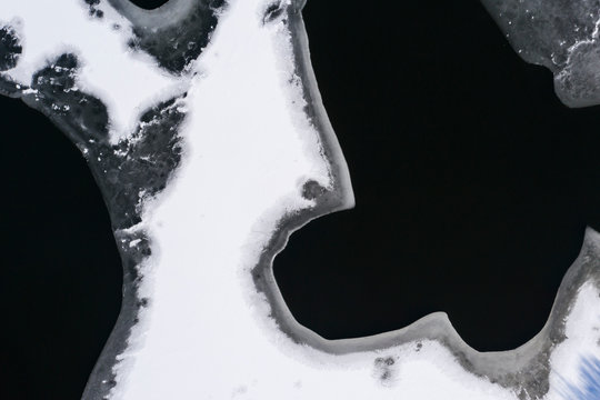 Flying above ice, top down aerial view of ice floes in the lake.