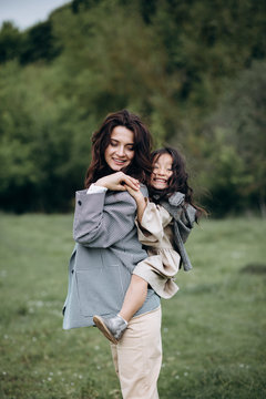 Portrait of hipster mother with daughter in her arms in the field. The family is having fun together
