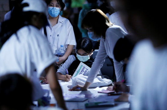 Student protesters line up to sign a petition that amends the country's constitution at a university in Bangkok