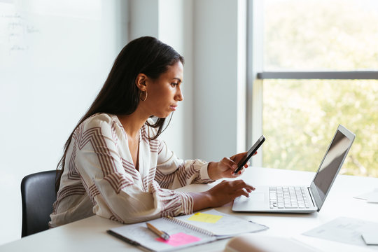 Event planner using smartphone and laptop in office