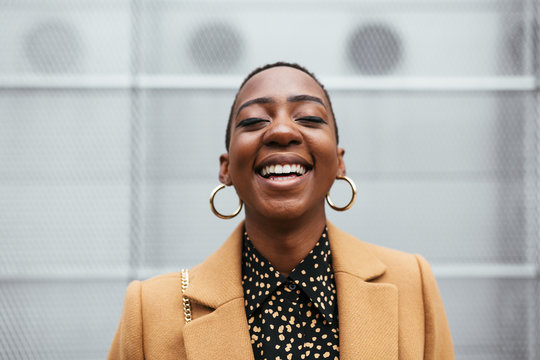 Delighted African American woman smiling on street