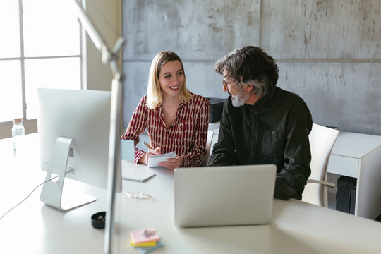 Cheerful trainee writing after mature mentor in office