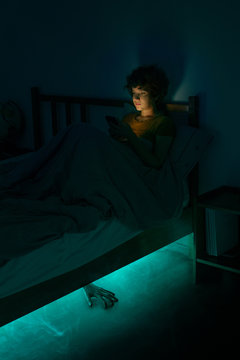 Helloween story. The girl uses a smartphone in bed, and monster crawls out from under the bed with mystical light and smoke.