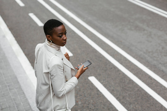 Black businesswoman with smartphone looking away near road