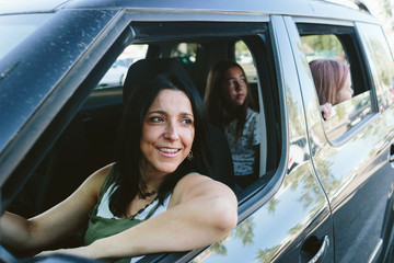 Mother and two teenage daughters on a car