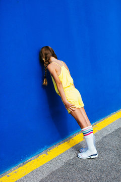 Trendy girl with pigtails leaning on bright wall on street