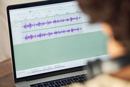 Podcaster editing audio files on laptop